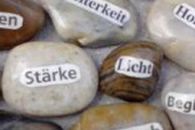 Das Bild zeigt Steine mit Aufschriften: Stärke, Licht, Heiterkeit ..